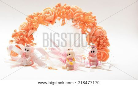 Decorative artificial flower garland with three cute baby dolls, Three cute baby dolls sitting in front of plastic flowers wreath