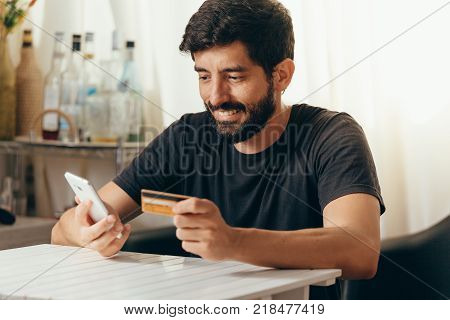 Online Payment. Man Holding A Credit Card And Using Smart Phone For Online Shopping