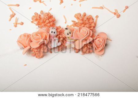 two baby dolls in artificial flowers wreath , isolated on white with copy space