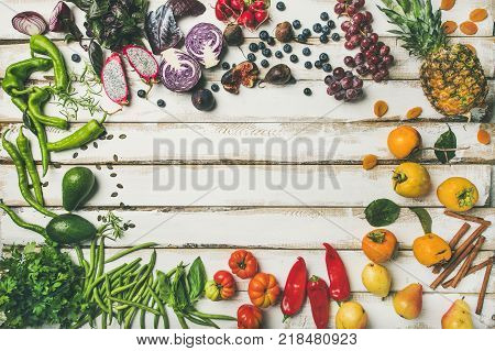 Helathy raw vegan food cooking background. Flat-lay of fresh fruit, vegetables, greens and superfoods over white wooden table, top view, copy space. Clean eating, vegetarian, alkaline diet concept