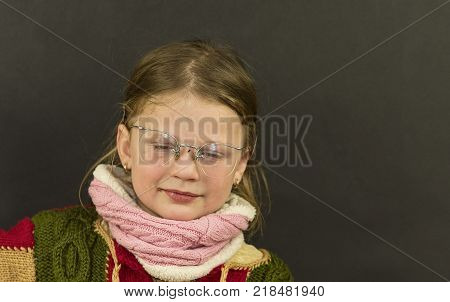 Portrait of attractive caucasian little girl with eyeglasses. Funny cute smiling child looking at camera on black background
