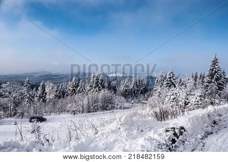 winter mountain landscape with snow covered road forest hills snow and blue sky with clouds on Bily kriz on czech - slovakian borders in Moravskoslezske Beskydy mountains