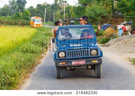 CHITWAN NEPAL - September 27 2013: Smiling people in the car on the road in the Royal Chitwan National Park. The park is 932 sq. km is mainly covered by jungle.