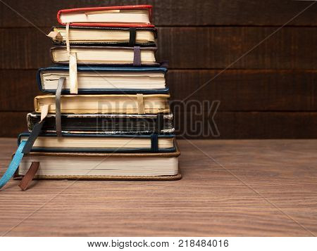 A stack of multicolored notebooks, neatly laid on a wooden table