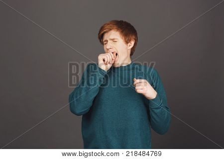 Portrait of young european attractive ginger guy with short haircut in green casual sweater clothing mouth with hand, yawning with closed eyes, being bored during long lecture in university