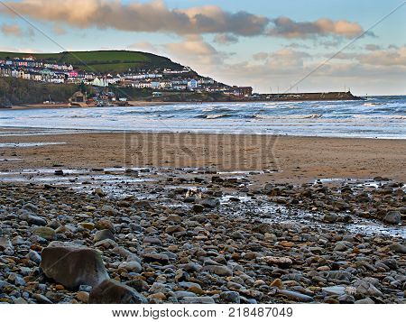 Panoramic view of New Quay harbour and pier from New Quay Bay one of the best beach walks in Wales. Also in the picture is the Lifeboat Station, fishing boats and the sandy cove used for water sports.