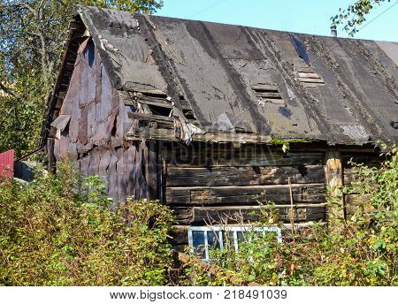 Old collapsing black barn with a leaky roof