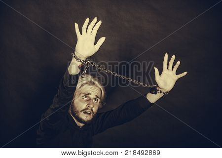 No freedom social problems concept. Furious man with chained hands studio shot on dark grunge background