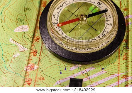 Touristic magnetic compass lying on topographical map