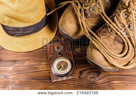 Touristic magnetic compass boots and hat on a rustic wooden table. Top view