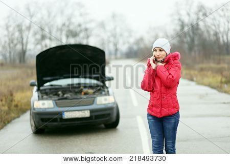 Problems with the car on the road. The girl evokes the tow truck for the car