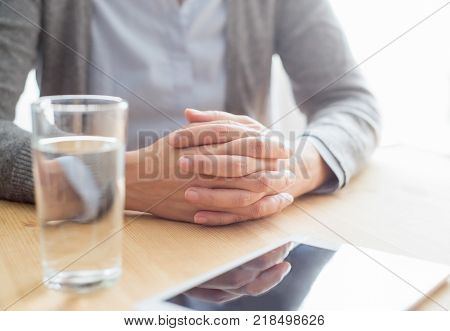 Cropped view of woman sitting at table with her hands clasped, glass of water and tablet