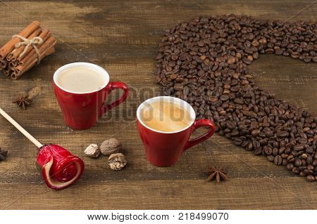 Two cups of coffee with a foam top view. Coffee beans badon cinnamon and caramel on a wooden surface. Love of a coffee drink. Morning invigorating coffee for two. Heart made of coffee beans.