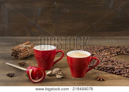 Two cups of coffee with a foam top view. Coffee beans badon cinnamon and caramel on a wooden surface with place for text. Love of a coffee drink. Morning invigorating coffee for two with copy space.