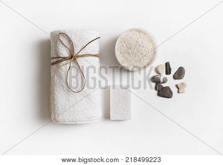 Beauty and spa concept. Towel sea salt pumice and stones on white paper background. Flat lay.