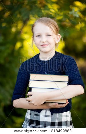 Adorable happy blond schooler girl ready back to school holding pile of textbooks school books manuals. Wearing school uniform. Warm september autumn day.
