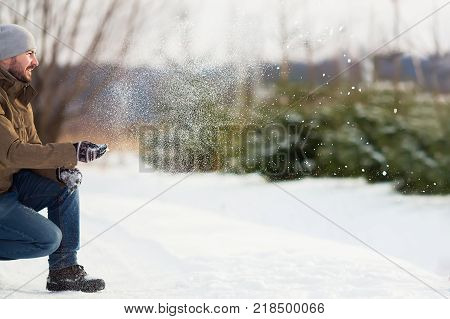 Handsome smiling man playing snowballs winter day family activity.