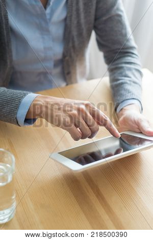 Cropped view of woman using touchpad and sitting at table with glass of water