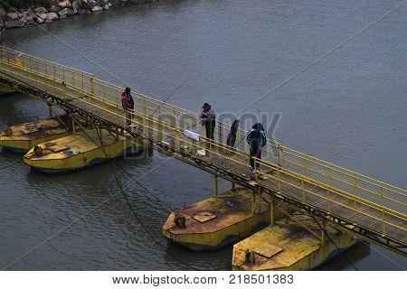 ARAD ROMANIA - DECEMBER 18 2015: Unidentified men fishing on a temporary bridge above Mures river in Arad Romania