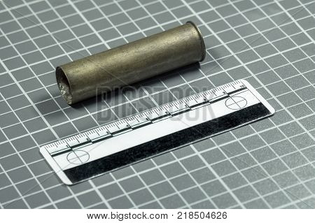 Close-up.The shot cartridge from the rifle and the forensic ruler lie on a green background with white lines for ballistic examination.