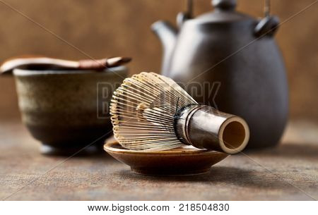 An arrangement of a traditional tea whisk and a ceramic tea pot