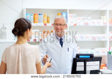 medicine, healthcare and people concept - smiling senior apothecary taking credit card from customer at pharmacy cash register