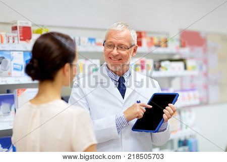 medicine, healthcare and technology concept - senior apothecary and female customer with tablet pc computer at pharmacy