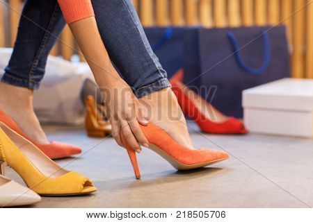 sale, shopping, fashion and people concept - young woman choosing high heeled shoes at store