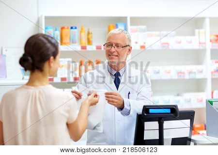 medicine, pharmaceutics, healthcare and people concept - senior apothecary with drug and female customer at pharmacy