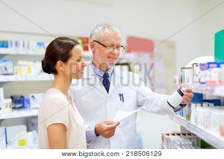 medicine, healthcare and people concept - senior apothecary with drug prescription and female customer at pharmacy