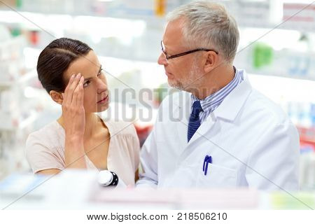 medicine, pharmaceutics, healthcare and people concept - senior apothecary offering drug for female customer suffering from headache at pharmacy