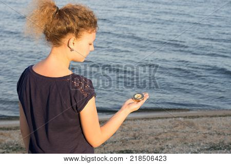 Girl holds a compass indicating the direction of the background of the sea