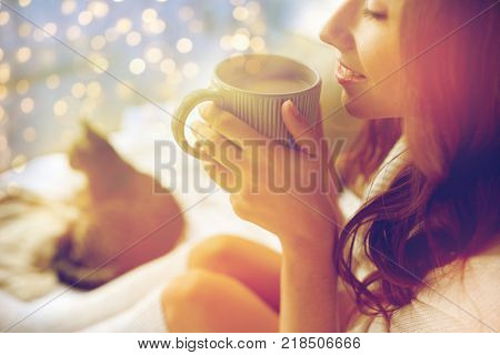winter, cosiness, leisure and people concept - close up of happy young woman with cup of coffee or cacao and cat in bed at home
