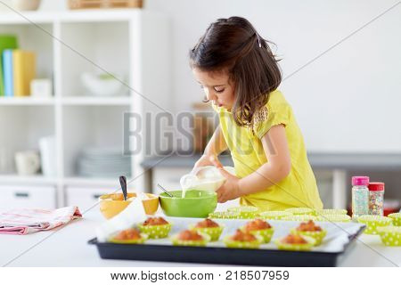 family, cooking, baking and people concept - little girl making batter for muffins or cupcakes and adding milk at home kitchen