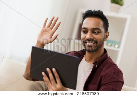 technology, people and lifestyle concept - happy man with tablet pc computer having video chat at home and waving hand