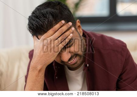 people, crisis, emotions and stress concept - close up of man suffering from head ache at home
