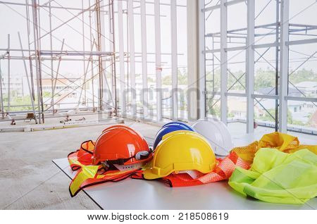 white orange yellow and blue safety helmet with reflective clothing on desk at construction site and scaffold background engineer safety industry and construction building concept