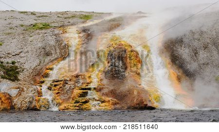 Bactreria and minerals create a colorful backdrop in the scalding hot run-off water of the Excelsior Geyser Crater as it flows into the Firehole River