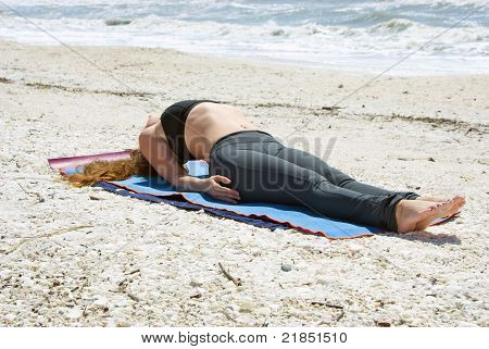 Woman Doing Yoga Exercise On Beach In Fish Pose