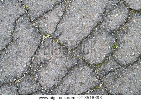 Closeup of damaged asphalt with many fissures on the road