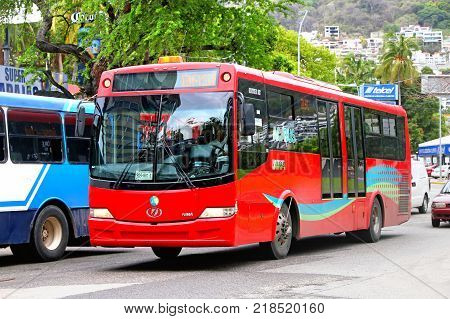 Acapulco Mexico - May 30 2017: Red urban bus Dina Linner 12 in the city street.