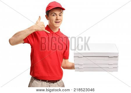 Teenage pizza boy with a stack of pizza boxes making a call me gesture isolated on white background