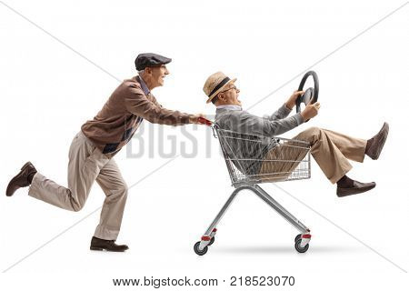 Senior pushing a shopping cart with another senior with a steering wheel riding inside isolated on white background