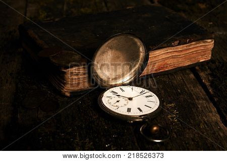 Old vintage pocket watch with an old antique bible book and ancient copper coins on a grunge wooden background. Antiques in an antique shop