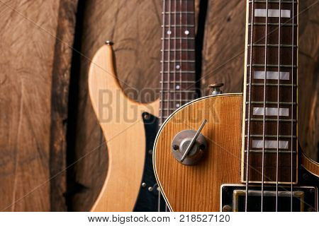 Wooden electric bass guitar and classic electric guitar on wooden background, string musical instrument, close-up