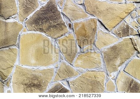 Wall with irregularly shaped Beige and brown tiles.