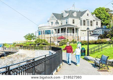 Bar Harbor, Usa - June 8, 2017: Senior Active Couple, Man, Woman Walking On Sidewalk By Oceanfront R
