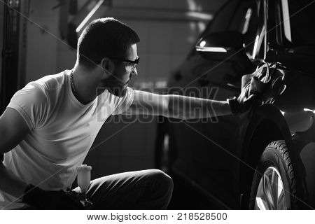 A man cleaning car with microfiber cloth, car detailing or valeting concept. Selective focus. poster