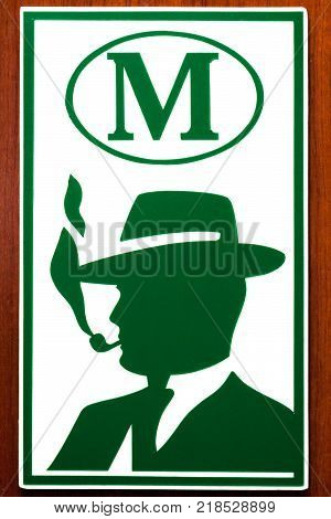 Plastic sign of a male toilet with a green silhouette of a man in a hat with a smoking pipe on a wooden door