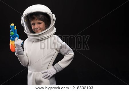Watchman. Waist up portrait of cosmonaut kid wearing protective costume and helmet is standing with arms akimbo and holding toy gun while looking at camera with joy. Isolated with copy space